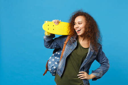Young african american girl teen student in denim clothes, backpack hold skate isolated on blue background studio portrait. Education in high school university college concept. Mock up copy space
