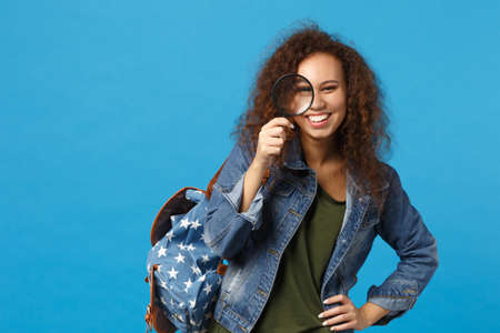Young african american girl teen student in denim clothes, backpack hold clock isolated on blue background studio portrait. Education in high school university college concept. Mock up copy space Stock fotó
