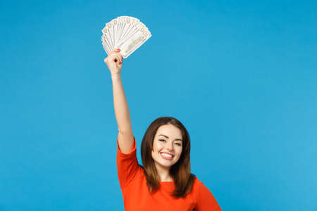 Beautiful brunette young woman wearing red orange dress holding fan of cash money in dollar banknotes isolated over blue wall background, studio portrait. People lifestyle concept. Mock up copy space