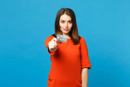 Beautiful brunette young woman wearing red orange dress hold in hand credit bank card isolated over trendy blue wall background, studio portrait. People lifestyle fashion concept. Mock up copy space 写真素材