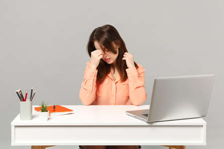 Young exhausted woman in pastel clothes keeping eyes closed, putting hand on nose sit work at desk with pc laptop isolated on gray background. Achievement business career concept. Mock up copy space Reklamní fotografie