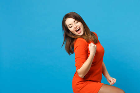 Beautiful excited brunette young woman wearing red orange dress doing winner gesture, say Yes isolated over blue wall background, studio portrait. People lifestyle fashion concept. Mock up copy space