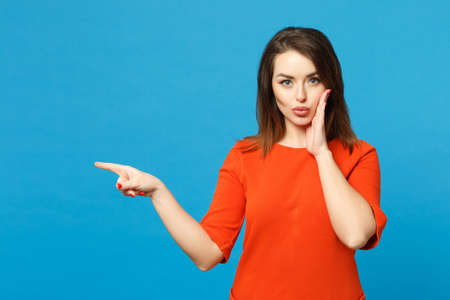 Beautiful young woman in red orange dress standing posing pointing hands fingers on workspace isolated over trendy blue wall background, studio portrait. People lifestyle concept. Mock up copy space