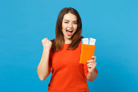 Beautiful brunette young woman wearing red orange dress hol in hand passport tickets isolated over trendy blue wall background, studio portrait. People lifestyle fashion concept. Mock up copy space Banque d'images