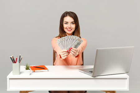 Young smiling woman holding fan of cash money in dollar banknotes, sit and work at desk with pc laptop isolated on gray background. Achievement business career lifestyle concept. Mock up copy space Reklamní fotografie