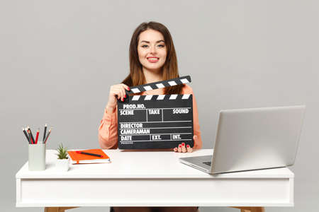 Young beautiful woman holding classic black film making clapperboard sit and work at desk with pc laptop isolated on gray background. Achievement business career lifestyle concept. Mock up copy space