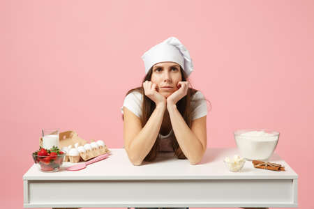 Sad tired female chef cook confectioner or baker in apron white t-shirt, toque chefs hat cooking cake or cupcake at table isolated on pink pastel background in studio. Mock up copy space food concept
