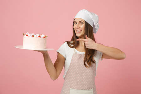 Housewife female chef cook confectioner or baker in apron white t-shirt, toque chefs hat hold in hand cake on stand plate isolated on pink pastel background in studio. Mock up copy space food concept Stock Photo