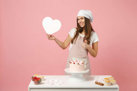 Chef cook confectioner or baker in apron white t-shirt, toque chefs hat cooking cake or cupcake at table hold like heart isolated on pink pastel background in studio. Mock up copy space food concept