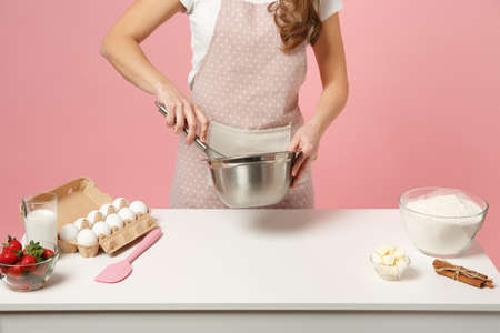 Cropped female chef cook confectioner or baker in apron white t-shirt, toque chefs hat cooking cake or cupcake at table isolated on pink pastel background in studio. Mock up copy space food concept Stock Photo