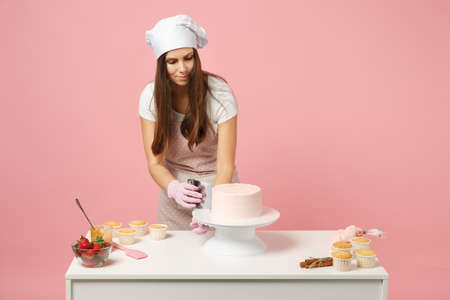 Chef cook confectioner or baker in white t-shirt, toque chefs hat cooking at table isolated on pink pastel background in studio. Cream application, cake making process. Mock up copy space concept