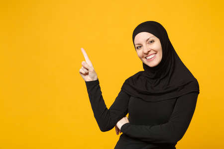 Smiling young arabian muslim woman in hijab black clothes showing pointing copy space with hands finger isolated on yellow background, studio portrait. People religious lifestyle concept. Mock up Reklamní fotografie