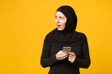 Smiling young arabian muslim woman in hijab black clothes hold in hands cellphone, chatting isolated on yellow wall background, studio portrait. People religious lifestyle concept. Mock up copy space Foto de archivo