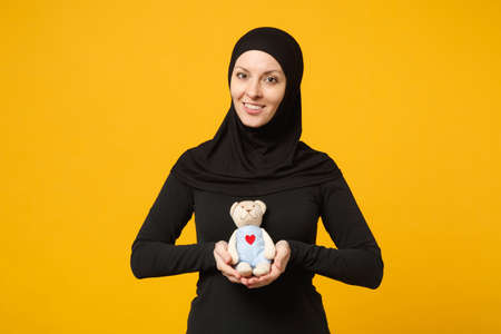 Smiling young arabian muslim woman in hijab black clothes hold in hands teddy bear plush toy isolated on yellow background, studio portrait. People religious lifestyle concept. Mock up copy space