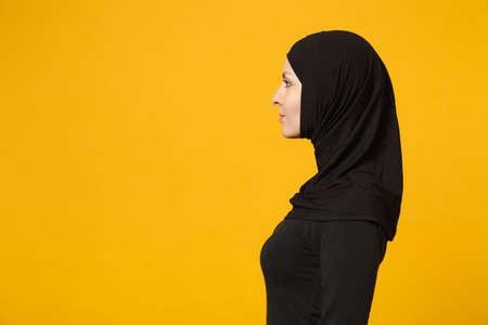 Immagine di vista laterale di bella giovane donna musulmana araba in vestiti neri di hijab che posano isolata sul fondo giallo della parete, ritratto dello studio. Concetto di stile di vita dell'Islam religioso della gente. Mock up copia spazio