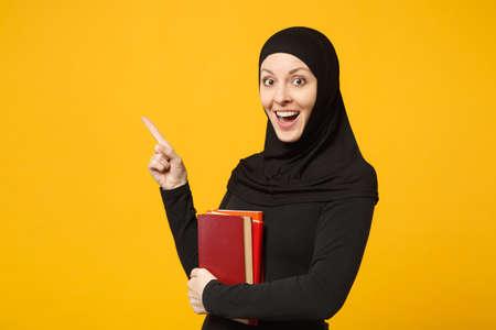 La ragazza studentessa musulmana araba in abiti neri hijab tiene libri isolati su sfondo giallo muro, ritratto in studio. Stile di vita religioso della gente, educazione nel concetto di scuola superiore. Mock up copia spazio