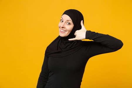 2cc977782 Smiling arabian muslim woman in hijab black clothes doing phone gesture  like says call me back