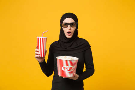 Arabian muslim woman in hijab black clothes 3d glasses watch movie film hold popcorn, cup of soda isolated on yellow wall background studio portrait. People lifestyle concept. Mock up copy space