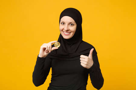 Young arabian muslim woman in hijab black clothes hold in hand holding bitcoin coin currency isolated on yellow background, studio portrait. People religious lifestyle concept. Mock up copy space