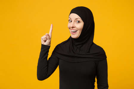 Smiling young arabian muslim woman in hijab black clothes pointing finger up, looking camera isolated on yellow background, studio portrait. People religious lifestyle concept. Mock up copy space