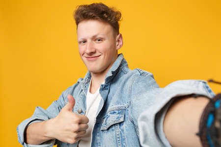 Close up selfie shot of smiling young man in denim casual clothes showing thumb up isolated on yellow orange wall background in studio. People sincere emotions lifestyle concept. Mock up copy space Banque d'images - 124534079