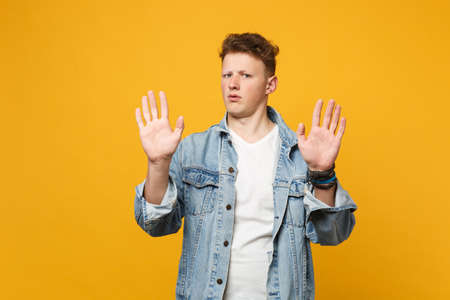 Portrait of concerned young man in denim casual clothes looking camera showing palms isolated on yellow orange wall background in studio. People sincere emotions lifestyle concept. Mock up copy space