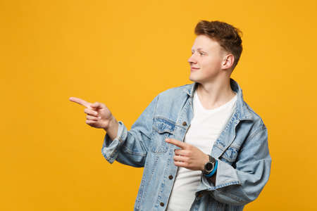 Portrait of smiling young man in denim casual clothes pointing index fingers aside isolated on yellow orange wall background in studio. People sincere emotions lifestyle concept. Mock up copy space