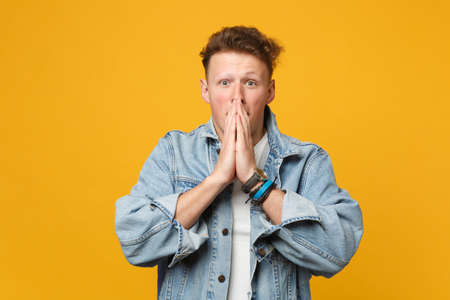 Portrait of shocked young man in denim casual clothes looking camera covering mouth with hands isolated on yellow orange wall background. People sincere emotions lifestyle concept. Mock up copy space Banque d'images - 124534280