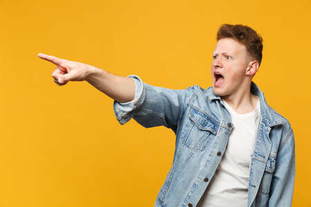 Portrait of shocked screaming young man in denim casual clothes pointing index finger aside isolated on yellow orange wall background. People sincere emotions, lifestyle concept. Mock up copy space
