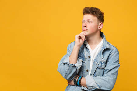 Portrait of pensive young man in denim casual clothes looking aside, put hand prop up on chin isolated on yellow orange wall background. People sincere emotions lifestyle concept. Mock up copy space Banque d'images - 124534285