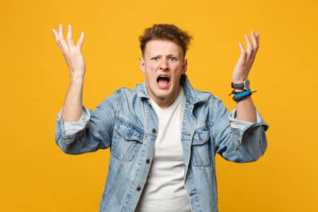 Portrait of irritated screaming young man in denim casual clothes looking camera, spreading hands isolated on yellow orange background. People sincere emotions, lifestyle concept. Mock up copy space