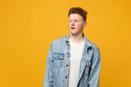 Portrait of bewildered young man in denim casual clothes looking aside keeping mouth open isolated on yellow orange background in studio. People sincere emotions lifestyle concept. Mock up copy space 版權商用圖片