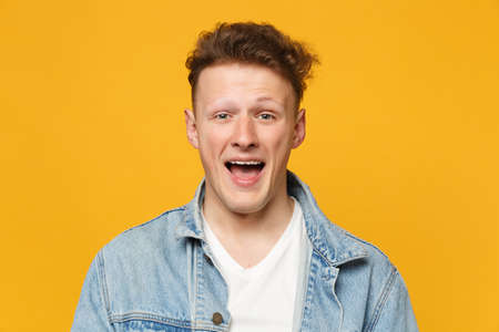 Portrait of cheerful excited young man wearing denim casual clothes looking camera isolated on yellow orange wall background in studio. People sincere emotions, lifestyle concept. Mock up copy space Banque d'images - 124534310