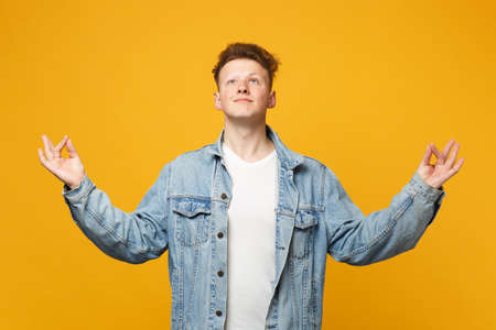 Handome young man in denim casual clothes looking up hold hands in yoga gesture relaxing meditating isolated on yellow orange background. People sincere emotions lifestyle concept. Mock up copy space 免版税图像 - 124534313