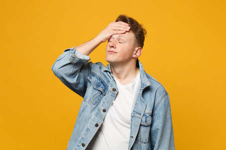 Portrait of tired young man in denim casual clothes keeping eyes closed, putting hand on head isolated on yellow orange wall background. People sincere emotions lifestyle concept. Mock up copy space