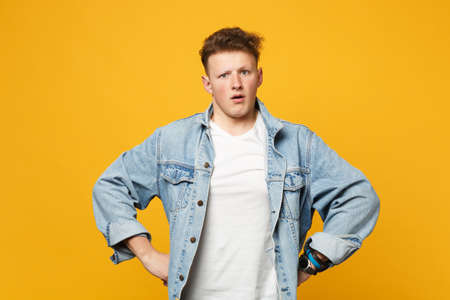 Portrait of shocked perplexed young man in denim casual clothes standing with arms akimbo isolated on yellow orange background in studio. People sincere emotions lifestyle concept. Mock up copy space