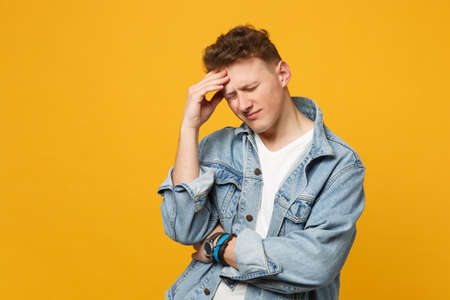 Portrait of tired young man in denim casual clothes keeping eyes closed, putting hand on head isolated on yellow orange wall background. People sincere emotions, lifestyle concept. Mock up copy space Banque d'images - 124534452