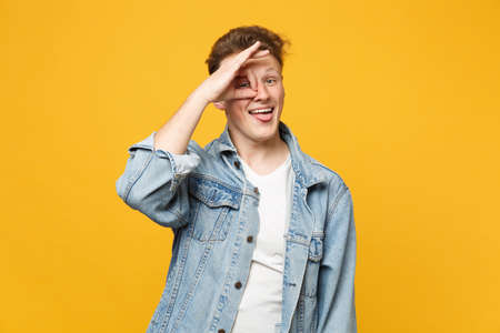 Cheerful young man in denim clothes showing tongue, holding hand near eyes, imitating glasses or binoculars isolated on yellow orange background. People sincere emotions concept. Mock up copy space 版權商用圖片