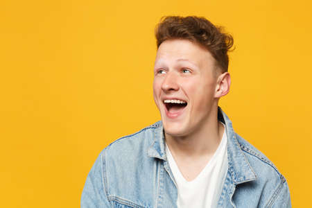Portrait of laughing funny young man wearing denim casual clothes looking aside isolated on yellow orange wall background in studio. People sincere emotions, lifestyle concept. Mock up copy space