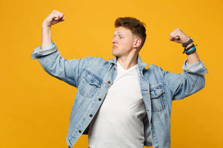 Portrait of strong young man in denim casual clothes looking aside, showing biceps, muscles isolated on yellow orange wall background. People sincere emotions lifestyle concept. Mock up copy space 版權商用圖片