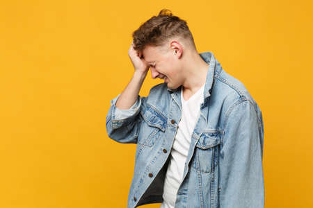 Side view of crying young man in denim casual clothes keeping eyes closed putting hand on head isolated on yellow orange wall background. People sincere emotions lifestyle concept. Mock up copy space 版權商用圖片