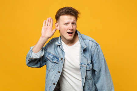 Portrait of curious young man in denim casual clothes try to hear you with hand near ear isolated on yellow orange background in studio. People sincere emotions lifestyle concept. Mock up copy space