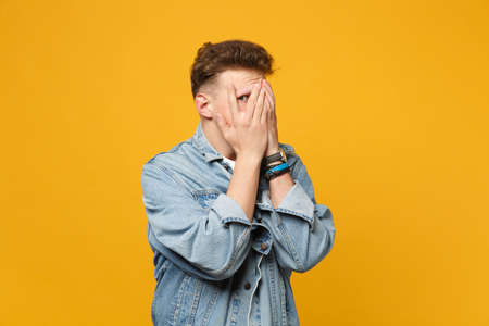 Portrait of peeping young man in denim casual clothes covering face with hands isolated on yellow orange wall background in studio. People sincere emotions, lifestyle concept. Mock up copy space