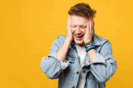Portrait of laughing young man in denim casual clothes keeping eyes closed, putting hands on head isolated on yellow orange background. People sincere emotions lifestyle concept. Mock up copy space