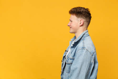 Side view of smiling handsome young man in denim casual clothes standing, looking aside isolated on yellow orange background in studio. People sincere emotions, lifestyle concept. Mock up copy space Standard-Bild - 124534470