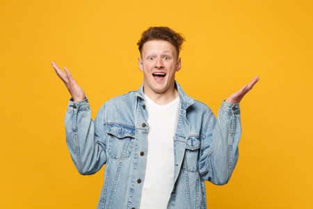 Excited young man in denim casual clothes looking camera, keeping mouth open, spreading hands isolated on yellow orange wall background. People sincere emotions, lifestyle concept. Mock up copy space