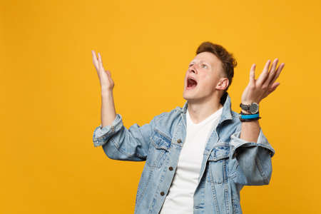 Irritated shocked young man in denim casual clothes looking up, spreading hands swearing isolated on yellow orange background in studio. People sincere emotions, lifestyle concept. Mock up copy space 版權商用圖片