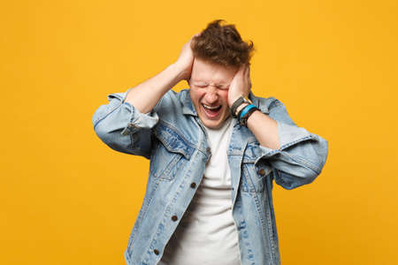 Frustrated young man in denim casual clothes keeping eyes closed, putting hands on head isolated on yellow orange background in studio. People sincere emotions, lifestyle concept. Mock up copy space