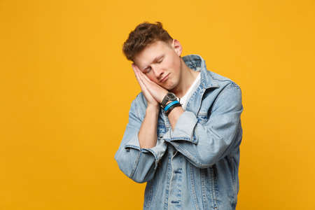 Portrait of relaxed young man in denim casual clothes sleep with folded hands under cheek isolated on yellow orange background in studio. People sincere emotions lifestyle concept. Mock up copy space 版權商用圖片