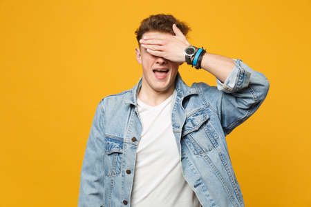 Portrait of funny young man in denim casual clothes keeping mouth open covering eyes with hand isolated on yellow orange wall background. People sincere emotions lifestyle concept. Mock up copy space